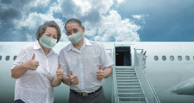 コロナウイルスのパンデミックを保護するためにマスクを持って旅行して幸せなアジアのシニア祖母と祖父