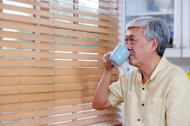 Senior asian man drinking coffee while standing in kitchen at home background, people lifestyle