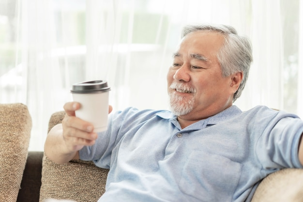 Senior asian man feel happy drinking hot coffee , hot latte , hot cappuccino , enjoy a cup of coffee on couch in the living room - lifestyle senior happiness concept