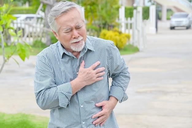 Старший азиатский человек, имеющий болезненный сердечный приступ грудной клетки в домашнем парке на открытом воздухе - концепция болезни сердца.
