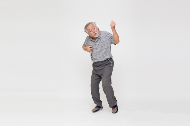 Старший азиатский мужчина слушает музыку в наушниках и танцует на белом фоне