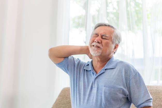 노인 아시아 남자, 그는 일어나 소파에 앉았고, 그는 올바른 자세가 아닌 베개에서 자서 목덜미에 통증을 느꼈다 - 노인들은 건강에 해로운 질병 개념