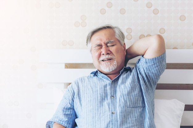Senior asian man , old man he wake up and sat on the bed , he had pain in the nape of his neck caused by sleeping on a pillow that is not correct posture - senior people unhealthy diseased concept