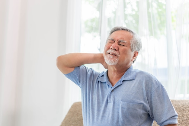 Senior asian man , old man he wake up and sat on sofa , he had pain in the nape of his neck caused by sleeping on a pillow that is not correct posture - senior people unhealthy diseased concept