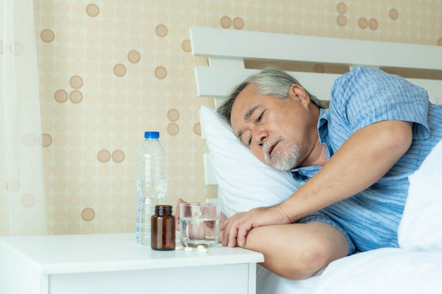 Senior asian man ,the old man was lying sick in his bed alone , beside his bed there was a table with a bottle of medicine and water - senior people unhealthy diseased concept