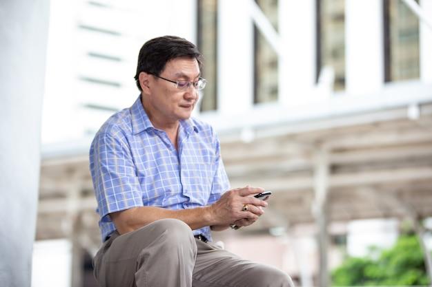 Старший азиатский мужчина с помощью мобильного телефона, сидя на открытом воздухе