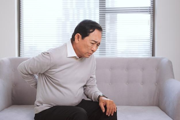 ソファに座って背中の痛みとアジアのシニア男性