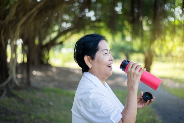 Senior asian woman drinking water after break workout at park,healthy elderly woman concept