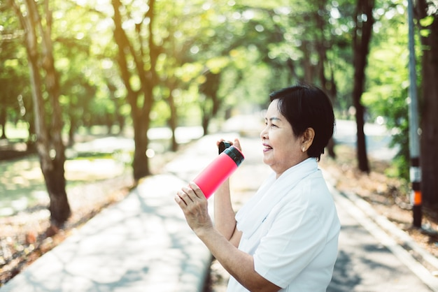 Senior asian woman drinking water after break workout at public park in the morning,healthy elderly women concept
