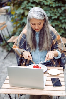 Senior asian woman eats toast with strawberries in front of laptop on outdoors cafe terrace