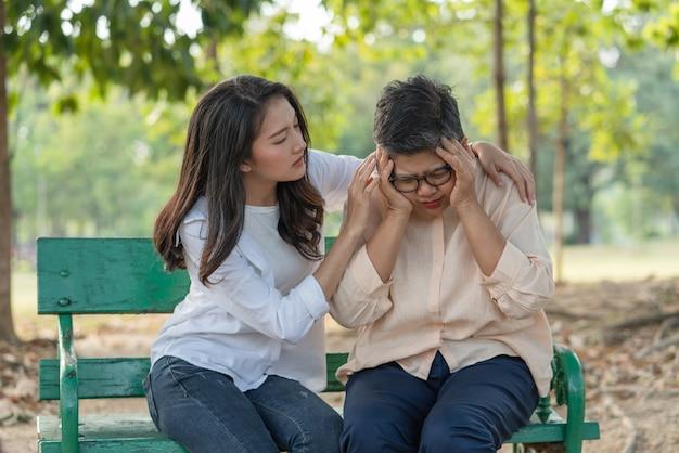 공원에서 벤치에 편안하게 앉아있는 동안 그녀의 딸의 도움과 지원으로 두통을 느끼는 수석 아시아 여자