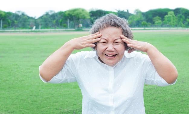 グリーンフィールドで屋外のシニアアジア女性幸せなアクション