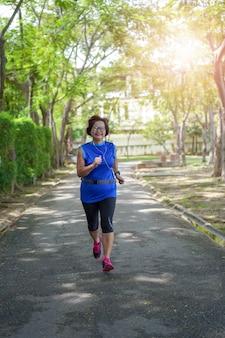 Senior asian woman happy jogging running in the park