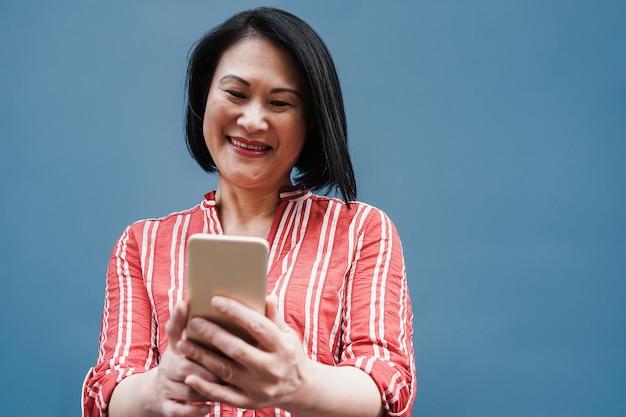 屋外で携帯電話を使って楽しんでいるアジアのシニア女性-顔に焦点を当てる