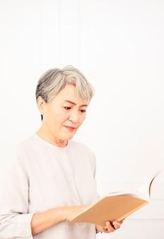 Старшая азиатская женщина держа и читая книгу.