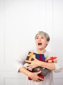 多くの最高のプレゼントを楽しんで、ギフトボックスのマウントを保持しているアジアのシニア女性。