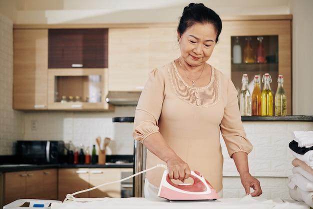 Старшая азиатская женщина гладит одежду