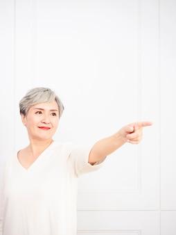 Старшая азиатская женщина указывая вверх 1 палец.