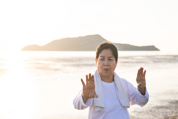Senior asian woman practicing tai chi exercise during sunset at the beach