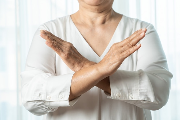 Senior asian woman say no holding two arms crossed