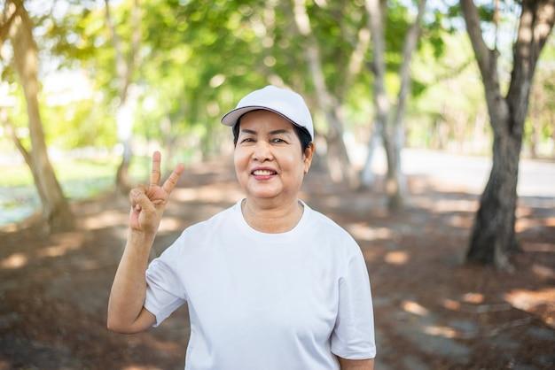 공공 공원에서 휴식을 취한 후 두 손가락을 보여주는 아시아 노인 여성, 건강한 노인 여성 개념