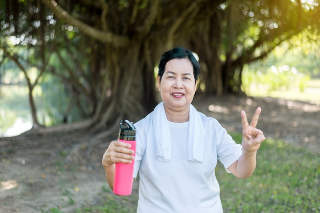 Senior asian woman showing two fingers and drinking water after break workout at park,healthy elderly woman concept