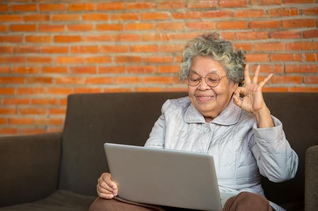 ソファに座っているアジアのシニアの女性は、ソーシャルネットワークを使用して自宅で自由な時間を過ごし、友人や子供たちとチャットして楽しんでいます。