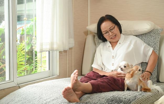수석 아시아 여자는 소파에 강아지와 함께 앉아, 그녀는 휴식과 미소.