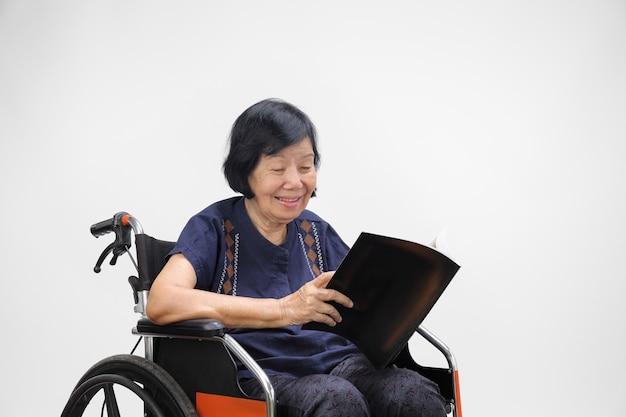화이트에 잡지를 읽는 동안 웃 고 수석 아시아 여자