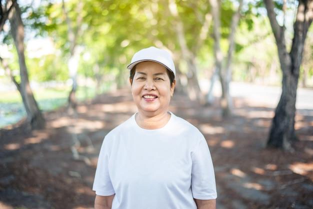공공 공원에서 휴식을 취한 후 서서 웃고 있는 고령의 아시아 여성, 건강한 노인 여성 개념