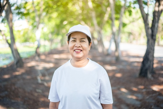 Senior asian woman standind and smiling after break workout at public park,healthy elderly woman concept