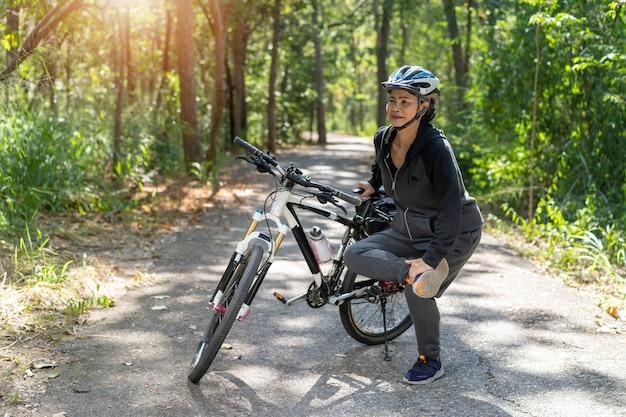 シニアアジアの女性は公園で自転車に乗って筋肉を伸ばす