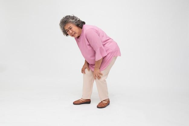 白い背景で隔離の膝の痛みに苦しんでいるアジアのシニア女性