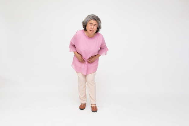 Senior asian woman suffering from stomachache isolated on white background