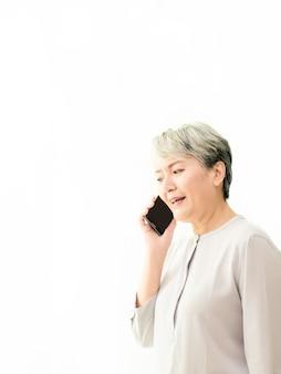 白い背景で彼女の携帯電話で話しているアジアのシニア女性。