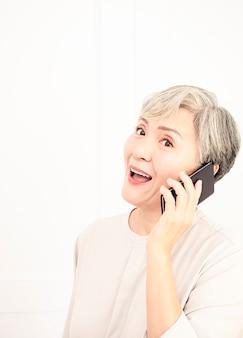 彼女の携帯電話で話しているアジアのシニア女性。年配の女性は携帯電話で幸せな会話をしています。