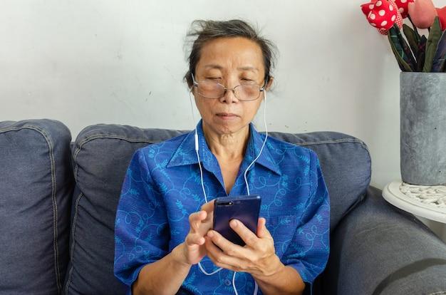 수석 아시아 여자는 휴대 전화를 사용하여 음악을 듣고 집에 소파에 앉아 소셜 미디어를 재생합니다.