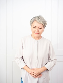 Senior asian woman wearing casual clothes with hand on stomach because indigestion, painful illness feeling unwell. ache concept.