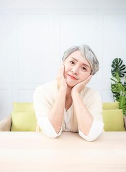 손에 턱을 대고 나무 테이블에 앉아 짧은 회색 헤어스타일을 가진 수석 아시아 여자.