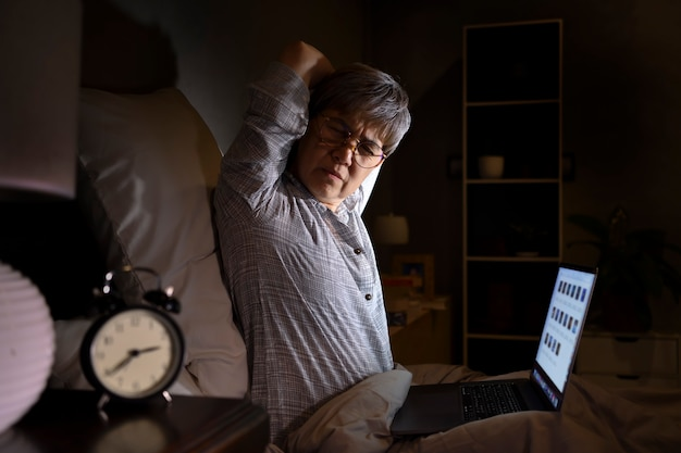Senior asian woman with sore and muscle pain from laptop use in bed