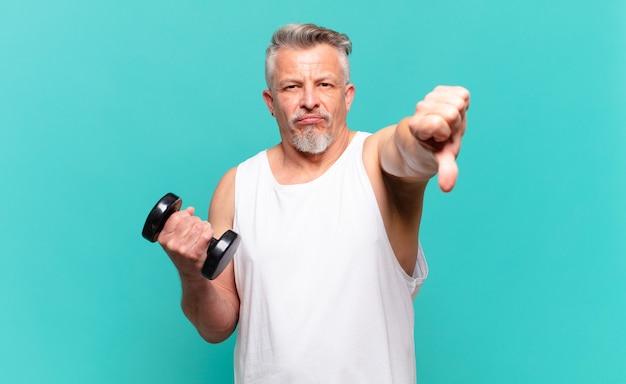 Старший спортсмен чувствует раздражение, злость, раздражение, разочарование или недовольство, показывая большие пальцы вниз с серьезным взглядом