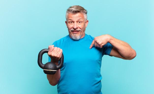 Старший спортсмен-мужчина чувствует себя счастливым, удивленным и гордым, указывая на себя взволнованным, изумленным взглядом