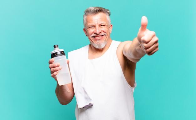 Старший спортсмен-мужчина чувствует себя гордым, беззаботным, уверенным и счастливым, позитивно улыбается с большими пальцами руки вверх