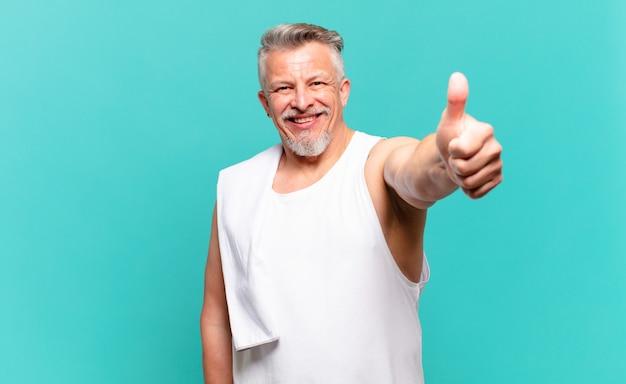 Старший спортсмен мужчина чувствует себя гордым, беззаботным, уверенным и счастливым, позитивно улыбается с большими пальцами руки вверх