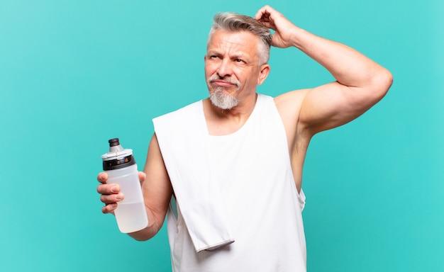 Старший спортсмен мужчина чувствует себя озадаченным и сбитым с толку, почесывает голову и смотрит в сторону
