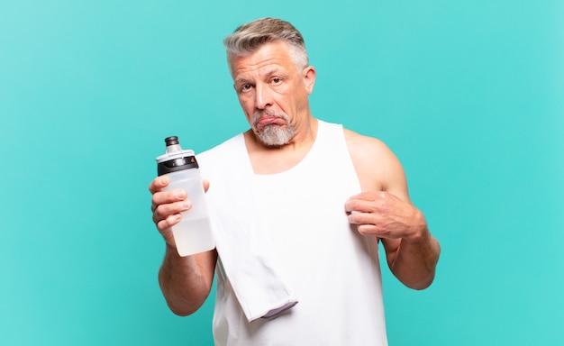 Старший спортсмен мужчина выглядит высокомерным, успешным, позитивным и гордым, указывая на себя