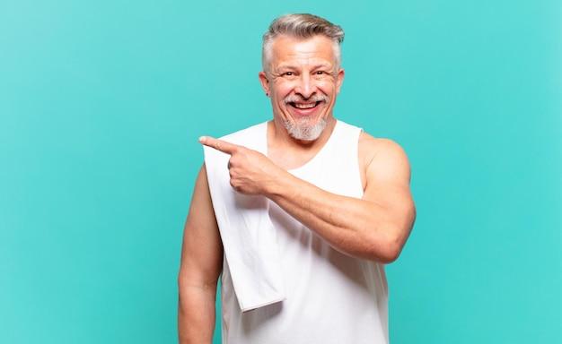 Старший спортсмен мужчина выглядит взволнованным и удивленным, указывая в сторону и вверх, чтобы скопировать пространство