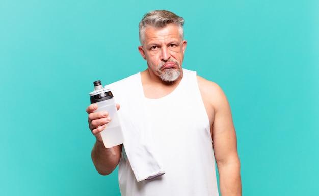 Старший спортсмен-мужчина выглядит озадаченным и сбитым с толку, прикусывает губу нервным жестом, не зная ответа на проблему