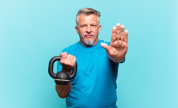 Senior athlete man looking serious, stern, displeased and angry showing open palm making stop gesture