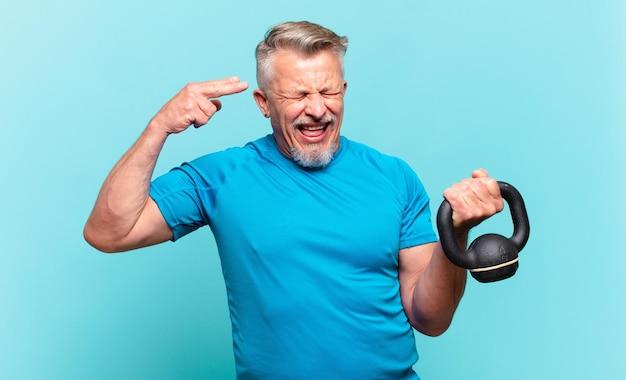 불행하고 스트레스를 받고 있는 시니어 운동선수 남자, 손으로 총기 표시를 하고 머리를 가리키는 자살 제스처